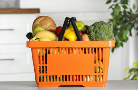 Shopping basket with grocery products on grey table indoors Imagens