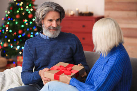 Happy couple opening Christmas gift at home Stock Photo