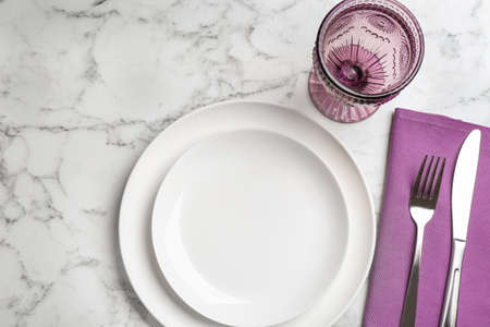 Elegant table setting on white marble background, flat lay Фото со стока