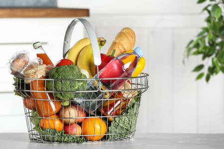 Shopping basket with grocery products on grey table indoors. Space for text