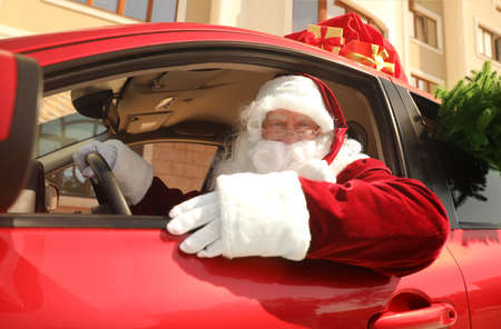 Authentic Santa Claus with fir tree and bag full of presents on roof driving modern car, outdoors Stock Photo