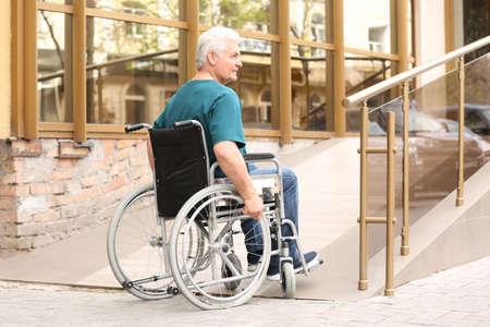 Senior man in wheelchair using ramp at building outdoors Banco de Imagens