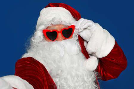 Authentic Santa Claus in sunglasses taking selfie on blue background