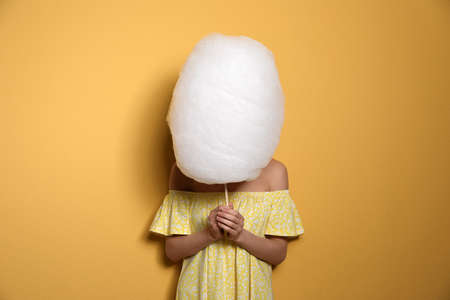Young woman hiding behind tasty cotton candy on yellow background