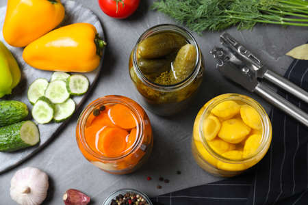 Flat lay composition with jars of pickled and fresh vegetables on grey table 写真素材