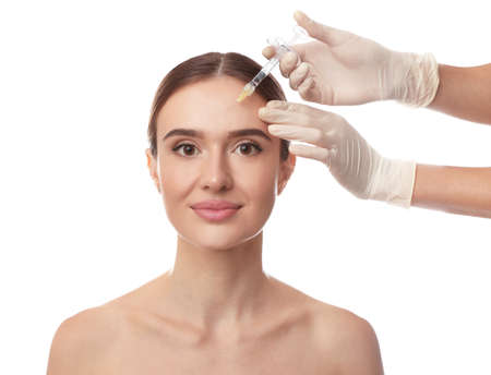 Beautiful woman getting facial injection on white background. Cosmetic surgery Stock Photo