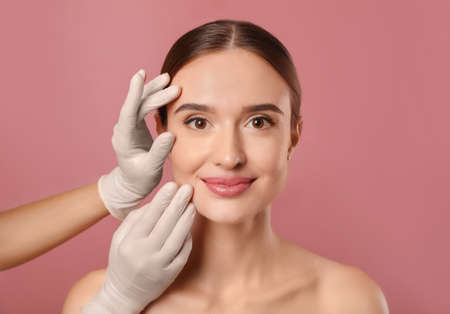 Doctor examining womans face before plastic surgery on pink background Фото со стока