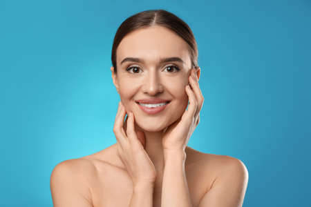 Beautiful woman with perfect smooth skin on light blue background Фото со стока