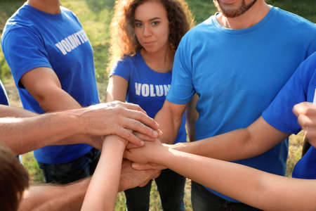 Group of volunteers joining hands together outdoors, closeup Stock fotó