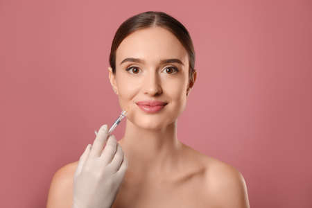 Beautiful woman getting facial injection on pink background. Cosmetic surgery