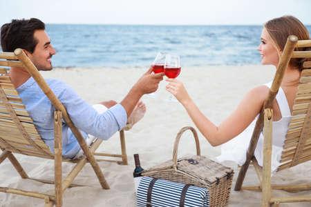 Glückliches junges Paar mit Gläsern Wein auf Liegestühlen am Meeresstrand sitzend
