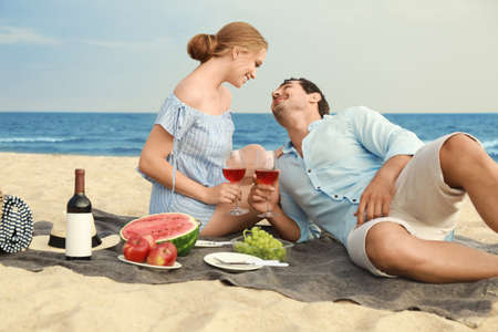 Beautiful young couple having picnic at sea beach