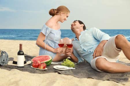 Schönes junges Paar, das Picknick am Seestrand hat