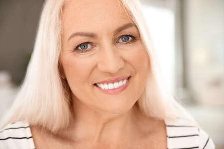 Retrato de mujer madura con bello rostro sobre fondo borroso, vista de cerca Foto de archivo