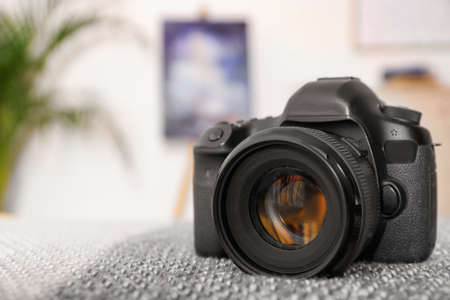 Professional digital camera against blurred background. Space for text