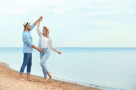 Happy romantic couple dancing on beach, space for text Stock Photo