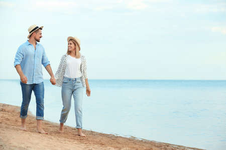 Happy romantic couple walking on beach, space for text