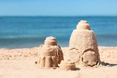 Sand figures on beach near sea. Space for text