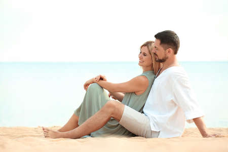 Happy romantic couple sitting together on beach