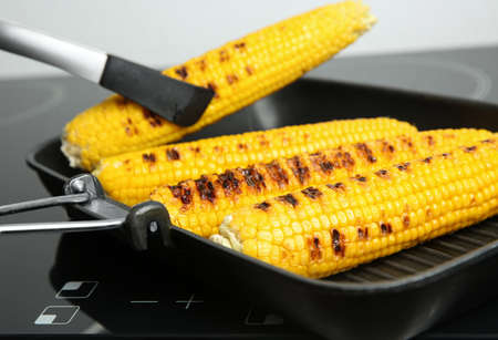 Cooking fresh corn cobs on grill pan, closeup