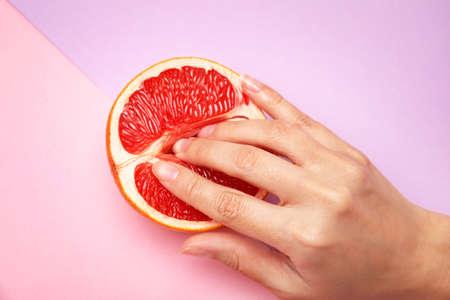 Jeune femme touchant la moitié du pamplemousse sur fond de couleur, vue ci-dessus. Notion de sexe Banque d'images