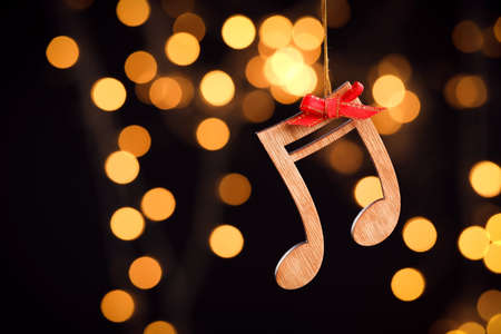 Wooden notes against blurred lights, space for text. Christmas music