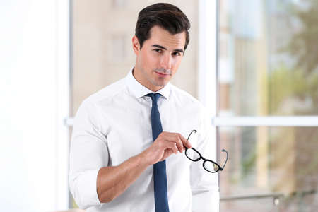 Handsome young man in stylish clothes with glasses indoors