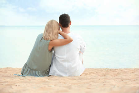 Happy romantic couple sitting together on beach, space for text Stock Photo