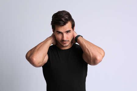 Portret van knappe jonge man in zwart t-shirt op grijze achtergrond Stockfoto