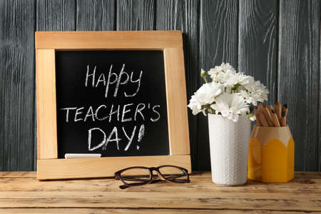 Chalkboard with inscription HAPPY TEACHERS DAY and vase of flowers on wooden table against grey wall Stock fotó