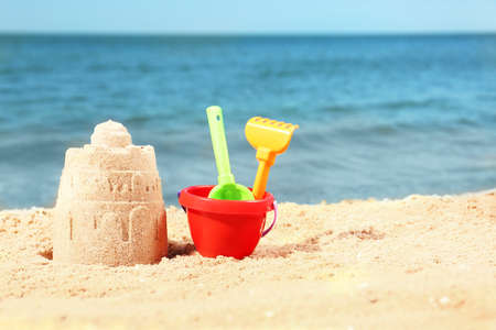 Beautiful view of beach with sand figure and plastic toys near sea. Space for text
