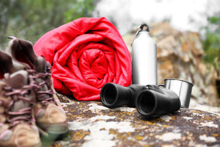Rolled sleeping bag and other camping gear outdoors
