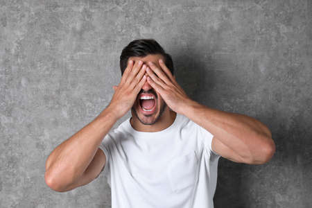 Young man being blinded and covering eyes with hands on grey background