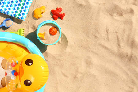 Flat lay composition with plastic beach toys and inflatable duck on sand. Space for text Stock fotó