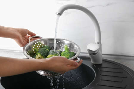 Woman washing fresh green broccoli in metal colander under tap water, closeup