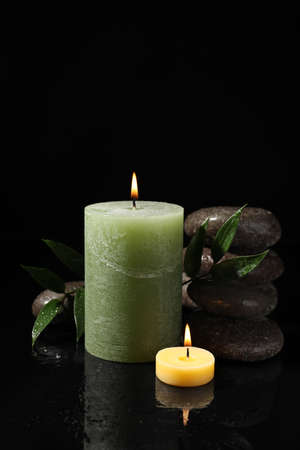 Composition with candles and spa stones on black background 写真素材