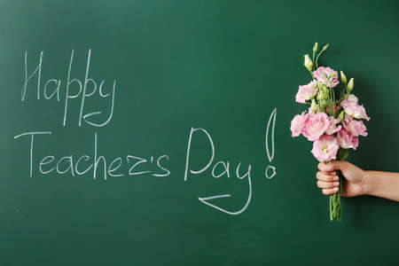 Woman holding flowers near green chalkboard with inscription HAPPY TEACHERS DAY, closeup view