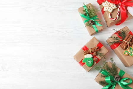 Flat lay composition with Christmas gift boxes on white wooden background. Space for text