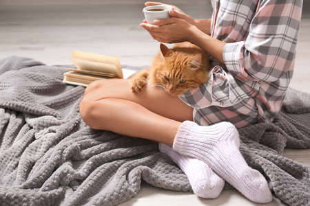 Woman with cute red cat and book on grey blanket at home, closeup view. Space for text Фото со стока