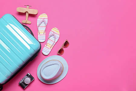 Blue suitcase and beach objects on pink background, flat lay. Space for text