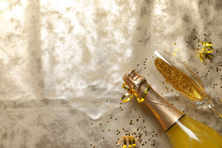 Flat lay composition with bottle of champagne for celebration on golden textile. Space for text Stock fotó