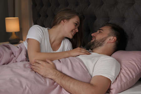 Young couple together in bed at nighttime