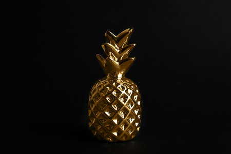 Gold metal decorative pineapple on black background