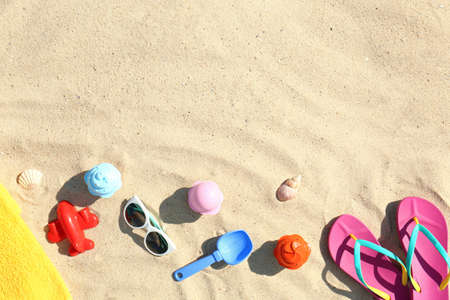 Flat lay composition with plastic beach toys on sand. Space for text