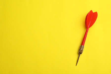 Red dart arrow on yellow background, top view with space for text