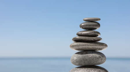 Stack of stones against blurred seascape, space for text. Zen concept