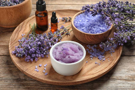 Plate with natural cosmetic products and lavender flowers on wooden table