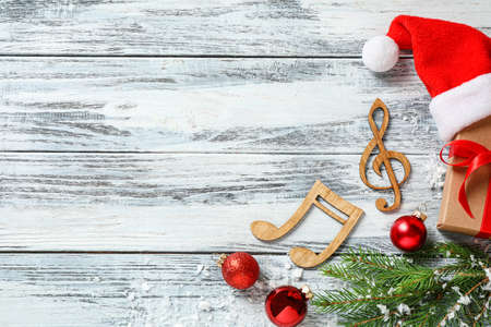Flat lay composition with notes on white wooden background, space for text. Christmas music concept