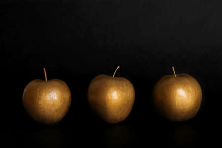 Gold painted fresh apples on black background