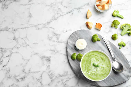 Flat lay composition with bowl of broccoli cream soup on white marble table, space for text